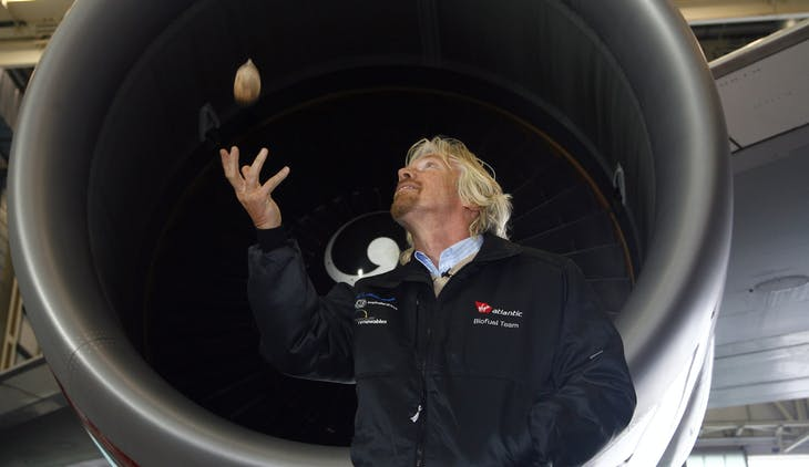 Virgin Group chairman Richard Branson throws a babassu nut in front of a Virgin Atlantic Boeing 747 aircraft, before the world's first commercial biofuel flight to Amsterdam from Heathrow Airport, in London February 24, 2008. Nuts picked from Amazon rainforests helped fuel the world's first commercial airliner flight powered by renewable energy on Sunday.     REUTERS/Luke MacGregor   (BRITAIN) - RTR1XI0O
