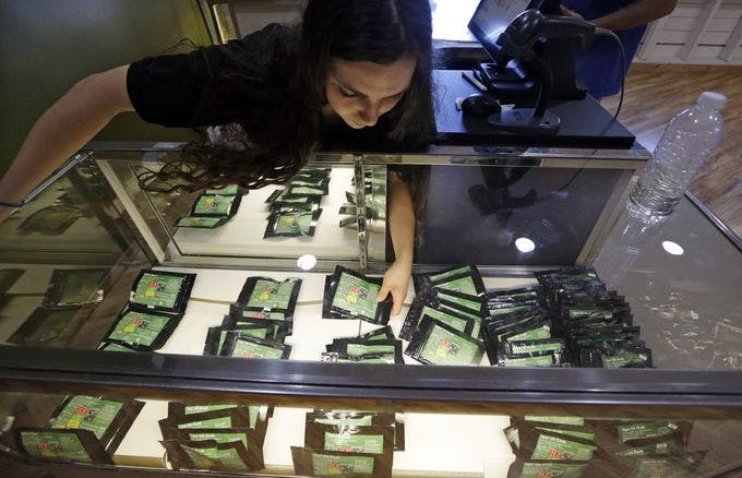 Clerk Havilah Nokes arranges packets of marijuana for sale at Cannabis City on the first day of legal recreational pot sales Tuesday, July 8, 2014, in Seattle. Washington on Tuesday became the second state to allow people to buy marijuana legally in the U.S. without a doctor's note as eager customers who lined up outside stores made their purchases. (AP Photo/Elaine Thompson)