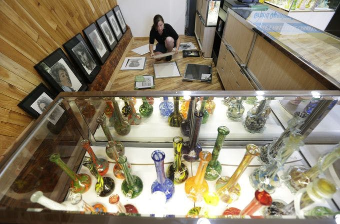 Krystal Klacsan prepares artwork to be hung, Monday, July 7, 2014 behind a case displaying glass bongs at the recreational marijuana store Cannabis City in Seattle. When legal sales begin on Tuesday, July 8, 2014, the store will be the first and only store in Seattle to initially sell recreational marijuana. (AP Photo/Ted S. Warren)