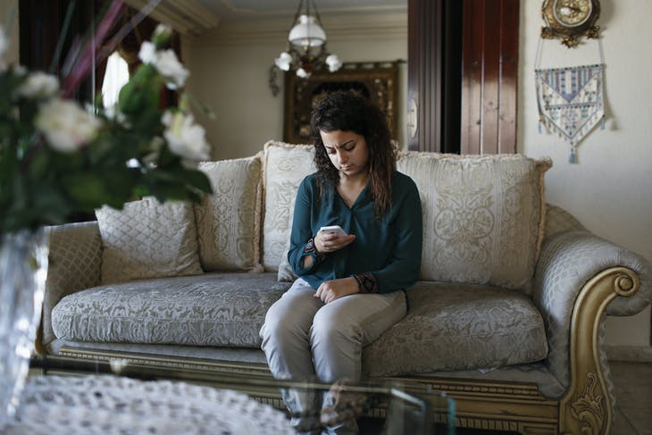 Farah Baker, 16, uses her phone to tweet in her family's home in Gaza City, August 10, 2014. As bombs explode in Gaza, Palestinian teenager Farah Baker grabs her smartphone or laptop before ducking for cover to tap out tweets that capture the drama of the tumult and fear around her. The 16-year-old's prolific posts on Twitter have made her a social media sensation through the month-old conflict. Once a little known high school athlete, Baker's following on the Web site has jumped from a mere 800 to a whopping 166,000. Picture taken August 10, 2014.   REUTERS/Siegfried Modola (GAZA - Tags: MEDIA SCIENCE TECHNOLOGY POLITICS CIVIL UNREST CONFLICT) - RTR41XSV