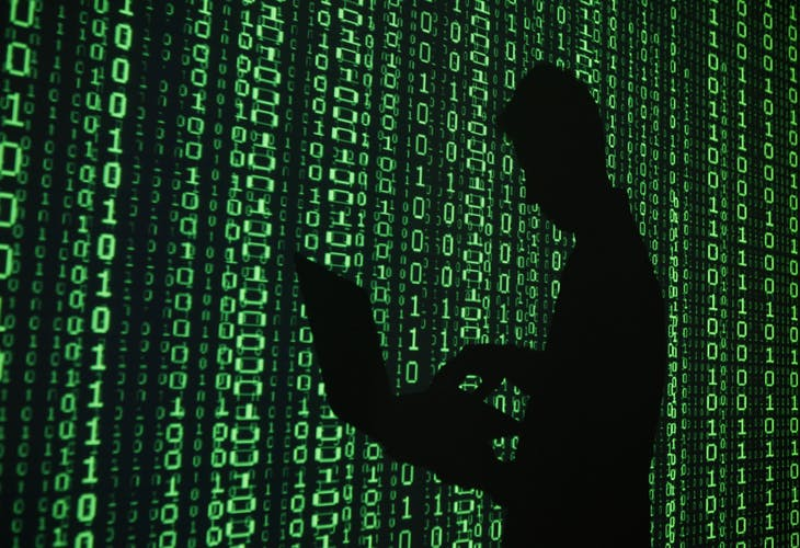 An illustration picture shows a projection of binary code around the shadow of a man holding a laptop computer in an office in Warsaw June 24, 2013. REUTERS/Kacper Pempel (POLAND - Tags: BUSINESS TELECOMS) - RTX10ZBN