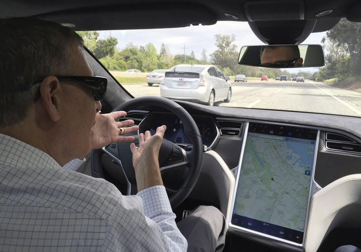 Reuters journalist Paul Ingrassia sits in the drivers seat of a Tesla S-Type in Autopilot mode in San Francisco, California, U.S., April 7, 2016.   To match Special Report AUTOS-DRIVERLESS/ REUTERS/Alexandria Sage - RTX2BPLY