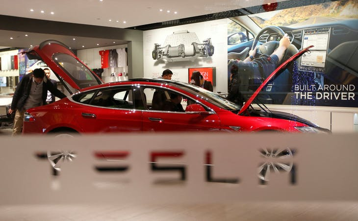 A man looks around Tesla Motors' Model S P85 at its showroom in Beijing January 29, 2014. REUTERS/Kim Kyung-Hoon/File Photo - RTSMACQ