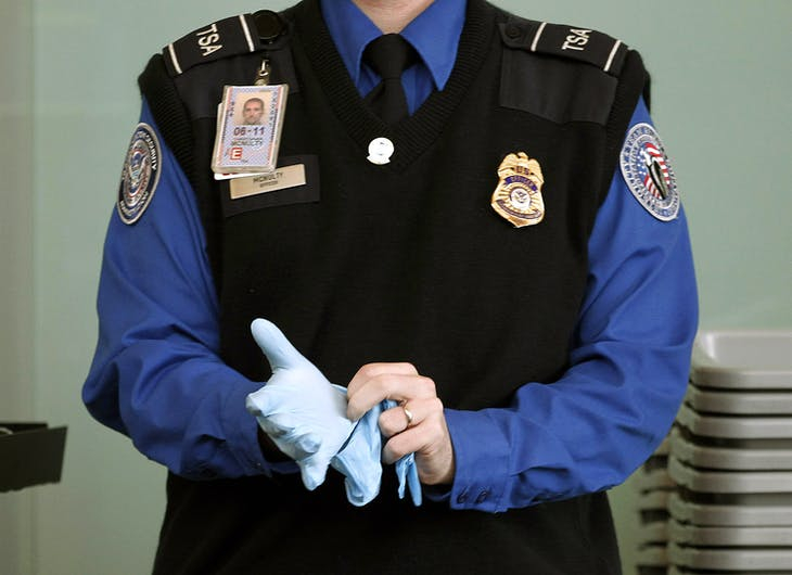 A TSA agent dons rubber gloves at a security checkpoint at Washington Reagan National Airport in Washington, November 22, 2010. U.S. authorities will reconsider airline passenger screening procedures that have caused public uproar on the eve of the busy holiday travel season, the top transport security official said on Monday.     REUTERS/Jason Reed   (UNITED STATES - Tags: POLITICS TRANSPORT CRIME LAW IMAGES OF THE DAY) - RTXUXTA