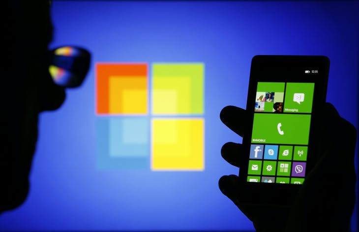 A man is silhouetted against a video screen with as he poses with a Nokia Lumia 820 smartphone in this photo illustration taken in the central Bosnian town of Zenica, September 3, 2013. Two years after hitching its fate to Microsoft's Windows Phone software, a withered Nokia collapsed into the arms of the U.S. software giant, agreeing to sell its main handset business for 5.44 billion euros ($7.2 billion). Nokia, which will continue as a maker of networking equipment and holder of patents, was once the world's dominant handset manufacturer but was long since overtaken by Apple and Samsung in the highly competitive market for more powerful smartphones. REUTERS/Dado Ruvic (BOSNIA AND HERZEGOVINA - Tags: BUSINESS TELECOMS TPX IMAGES OF THE DAY) - RTX135K5
