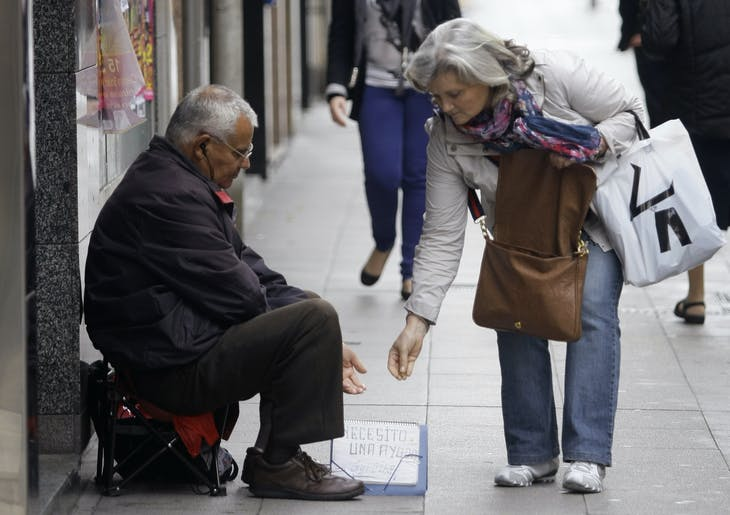 A woman gives money to a beggar on a street in Pontevedra, northwest Spain June 15, 2012.      REUTERS/Miguel Vidal (SPAIN - Tags: BUSINESS SOCIETY POVERTY) - RTR33NLH