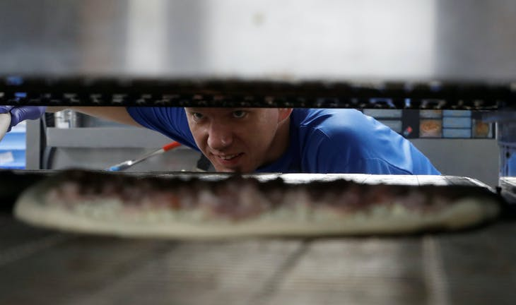 A staff member prepares a pizza at a Domino's Pizza restaurant in Moscow, Russia, July 14, 2017. Picture taken July 14, 2017. REUTERS/Sergei Karpukhin - RC1CB9D20250