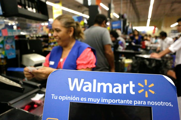 A cashier smiles beyond a Walmart logo during the kick-off of the 'El Buen Fin' (The Good Weekend) holiday shopping season, at a Walmart store in Monterrey, Mexico, November 17, 2017. REUTERS/Daniel Becerril - RC1E25779E80