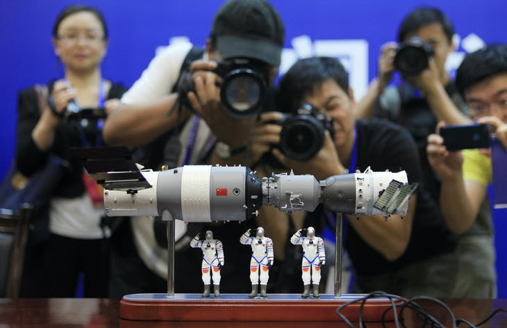 Photographers take pictures of a model of the Shenzhou-9 manned spacecraft ( R) docking with the orbiting Tiangong-1 space lab module (L) and three Chinese astronauts after a news conference at Jiuquan Satellite Launch Center, in northwest China's Gansu province, June 15, 2012. The Shenzhou-9 manned spacecraft will be launched at 18:37 (10:37 GMT) on June 16, 2012, according to a decision made by China's manned space docking program headquarters, Xinhua News Agency reported. REUTERS/Jason Lee (CHINA - Tags: SCIENCE TECHNOLOGY) - GM2E86F19E901