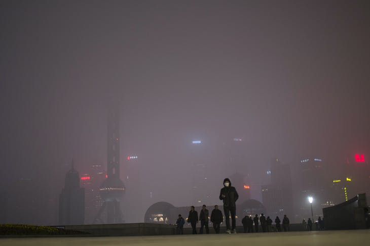 """A man wears a face mask while walking on the Bund in front of the financial district of Pudong, during a hazy day in downtown Shanghai January 25, 2015. China's pollution crisis has inspired an environmental regulator in a smog-blanketed northern province to write a novel whose extracts have gone viral online, spurring plans for two more books. """"Smog Is Coming"""", published last June, touches on fraud and bureaucracy and their impact on air pollution, with the official China Daily reporting that online excerpts have received tens of millions of pageviews. REUTERS/Aly Song (CHINAENVIRONMENT SOCIETY - Tags: ENVIRONMENT POLITICS SOCIETY) - GM1EB1P1Q9D01"""
